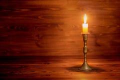 与葡萄酒黄铜烛台的灼烧的老蜡烛在木后面 免版税库存图片