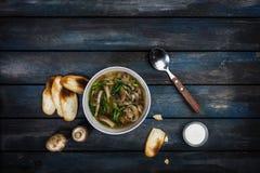 与葱酸性稀奶油和面包油炸马铃薯片的新鲜的蘑菇汤 在与利器的白色碗dishe 上色木 库存图片