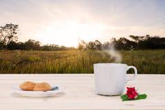与蒸汽、点心和红色花的热的咖啡与在葡萄酒木台式的绿色叶子在日出期间的被弄脏的草甸 图库摄影