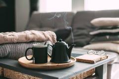 与蒸汽的茶在屋子里在早晨阳光下 库存图片