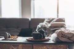 与蒸汽的茶在屋子里在早晨阳光下 库存照片