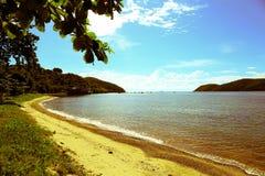 与蓝天、云彩、树和山的海海滩 免版税库存图片