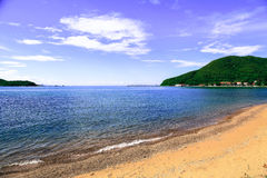 与蓝天、云彩和山的海海滩,作为自然 免版税库存图片