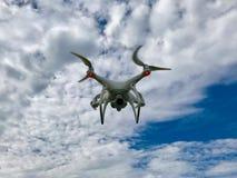与蓝天和云彩的白色寄生虫quadcopter 库存照片