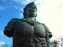与蓝天和云彩的Wisnu雕象 免版税库存照片