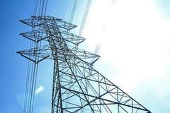与蓝天和工程学backgro的高压电杆 库存照片
