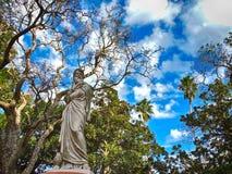 与蓝天和树的雕塑 免版税库存图片