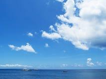 与蓝天和波纹的海水风景 与白色小船的海滨视图 免版税库存照片