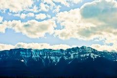与蓝天和白色云彩的山 免版税库存照片