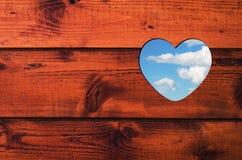 与蓝天和白色云彩的心形的孔在棕色木墙壁 免版税库存图片