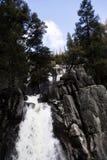 与蓝天白色的瀑布覆盖绿色树 库存照片