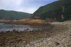 与蓝天的小卵石石海滩 图库摄影
