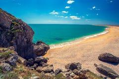 与蓝天的岩石海滨 离开的海滩 库存图片