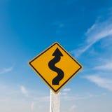 与蓝天的弯曲道路标志 库存图片