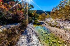 与蓝天的秋叶之前围拢的一条岩石小河的宽射击在失去的槭树 免版税库存照片