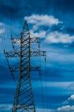与蓝天的高压输电线塔在backgound 库存照片