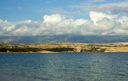 与蓝山山脉和大白色云彩的沿海风景 免版税库存照片