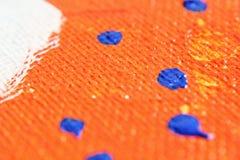 与蓝色下落的橙色丙烯酸漆 库存图片