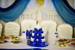 与蓝色丝带的新婚佳偶婚宴喜饼和小雕象tabl的 图库摄影