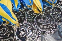 与蓝色丝带的许多银牌在一个银色盘子 免版税库存图片