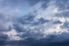 与蓝色云彩和白色的风雨如磐的天空在背景突出 图库摄影