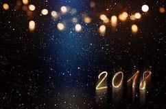 与蓝色光束和金黄bokeh的新年背景 库存图片