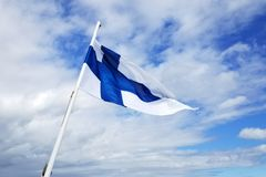 与蓝色十字架的白旗在天空蔚蓝背景 免版税库存照片