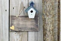 与蓝色和白色鸟舍的空白的标志在树旁边 免版税图库摄影