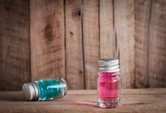 与蓝色和红色液体的两不可思议的玻璃魔药在木桌上 免版税库存图片