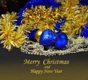 与蓝色和金黄球和闪亮金属片的圣诞节明信片 免版税图库摄影