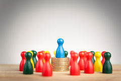 与蓝色图的富有的商业领袖概念在硬币sta顶部 库存图片