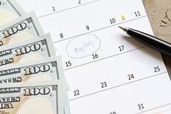 与蓝色圆识别标的日历在词发薪日和美国美元兑现金钱为提醒 库存照片