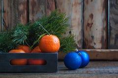 与蓝色圣诞节球的蜜桔在葡萄酒箱子 库存图片