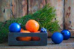 与蓝色圣诞节球的蜜桔在葡萄酒箱子 免版税库存图片