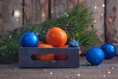 与蓝色圣诞节球的蜜桔在葡萄酒箱子 库存照片