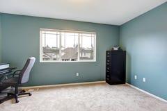 与蓝色墙壁的简单的家庭办公室室内部。 免版税库存照片