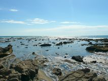 与蓝色多云天空以色列的岩石&沙滩 免版税库存图片