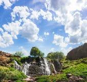 与蓝色多云天空的山瀑布 库存图片