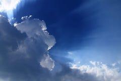 与蓝色太阳光芒和动态云彩的美丽的天空 免版税库存图片