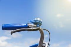 与蓝色夹子的蓝色自行车响铃在把柄酒吧 图库摄影