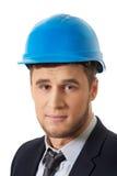 与蓝色安全帽的愉快的商人 免版税图库摄影