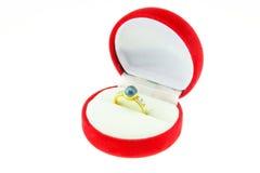 与蓝色宝石的金戒指在白色隔绝的红色箱子 免版税库存照片