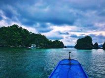 与蓝色小船和乌云的跳岛战术 库存照片