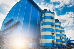 与蓝色工厂仓库的工业储水箱 储水箱设施 库存图片