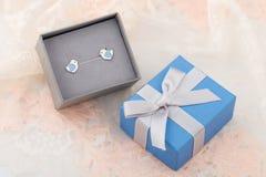 与蓝色心脏耳环螺柱的鸟形状在鞋带bac的礼物盒 免版税库存图片