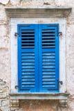 与蓝色快门的一个古老窗口 免版税图库摄影