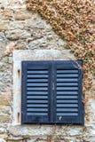 与蓝色快门的一个古老窗口 免版税库存照片