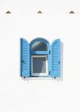 与蓝色快门的窗口在白色墙壁上 免版税库存图片