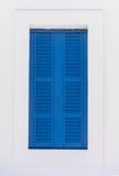 与蓝色快门的窗口在白色墙壁上 免版税库存照片