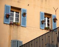 与蓝色快门的窗口在米黄墙壁上在马赛 免版税库存图片
